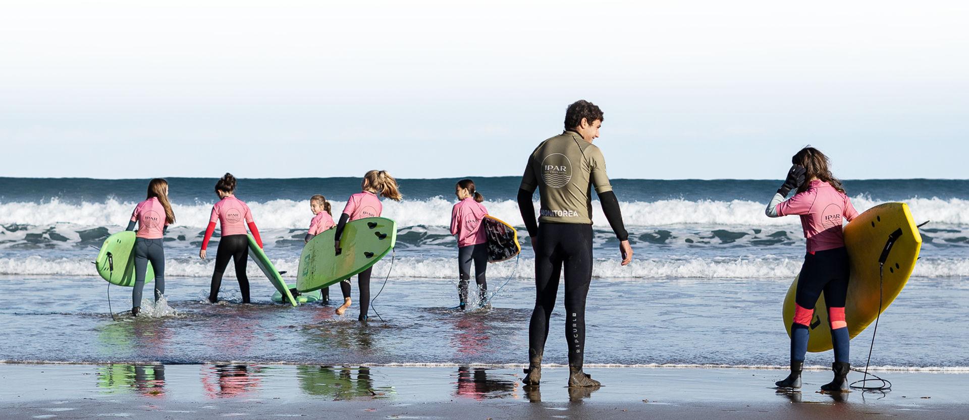 Grupo clase de surf de la escuela de surf IPAR en Deba Guipuzcoa